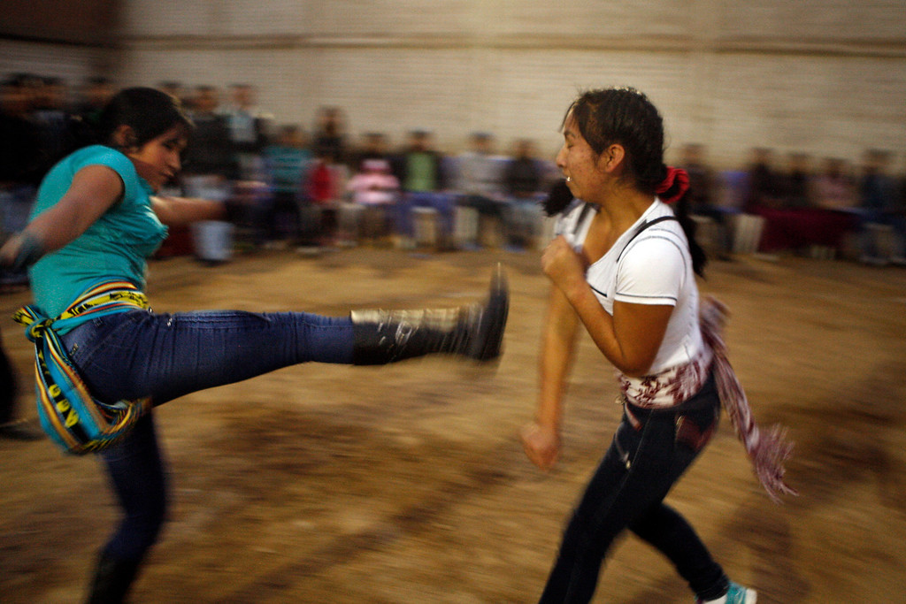. Inelda Flores, right, and Sandra Palermo take part in a Takanakuy ritual fight in Lima, Peru. It\'s not just adult males who fight. Women and children with scores to settle also battle it out. (AP Photo/Karel Navarro)