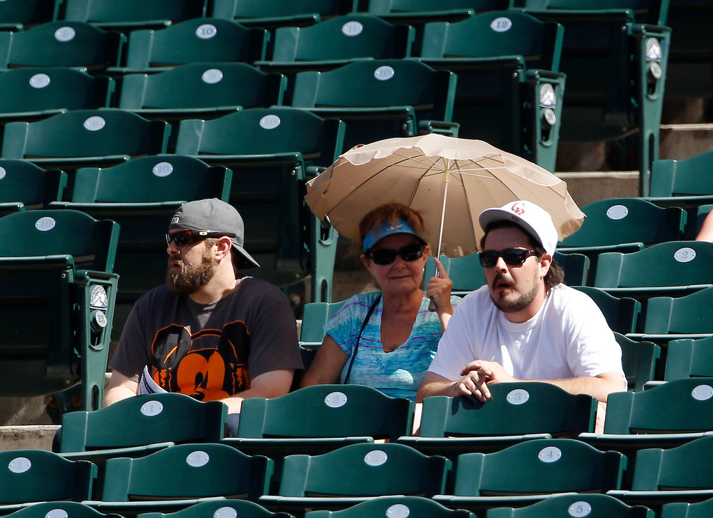 . Fans seek cover with an umbrella as temperatures hit the century mark as the New York Mets face the Colorado Rockies in the first inning of a baseball game in Denver on Thursday, June 27, 2013. (AP Photo/David Zalubowski)