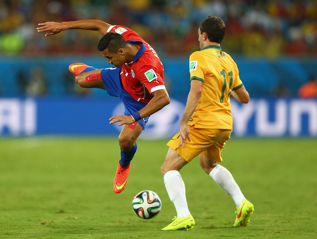 . Alexis Sanchez of Chile falls after a challenge with Tommy Oar of Australia during the 2014 FIFA World Cup Brazil Group B match between Chile and Australia at Arena Pantanal on June 13, 2014 in Cuiaba, Brazil.  (Photo by Clive Brunskill/Getty Images)