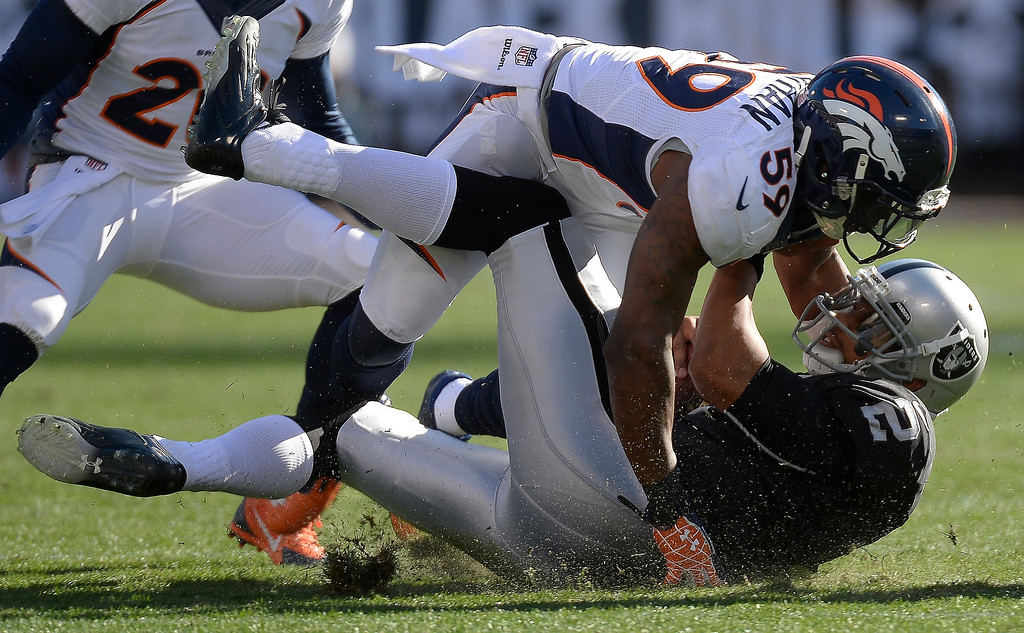 . Oakland Raiders quarterback Terrelle Pryor (2) gets hit by Denver Broncos outside linebacker Danny Trevathan (59) after picking up a few yards during the first quarter at O.co Coliseum. (Photo by John Leyba/The Denver Post)