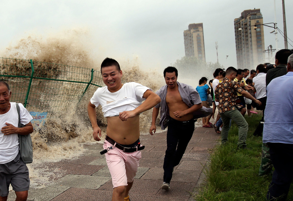 ". This picture taken on August 22, 2013 shows onlookers running away from huge waves from the ""Haining tide\"" - a daily occurrence when the river tides hit the banks of the city - as they surge higher than usual due to the influence of Typhoon Trami in the region in Haining, in eastern China\'s Zhejiang province. Typhoon Trami, the 12th typhoon to hit China this year, brought rainstorms and wreaked havoc in eastern China after landing in Fujian Province early on August 22.  The tides there have attracted spectators for the past two millennia, and it is the scene of an annual Tide-Watching Festival in late summer.      AFP PHOTOSTR/AFP/Getty Images"
