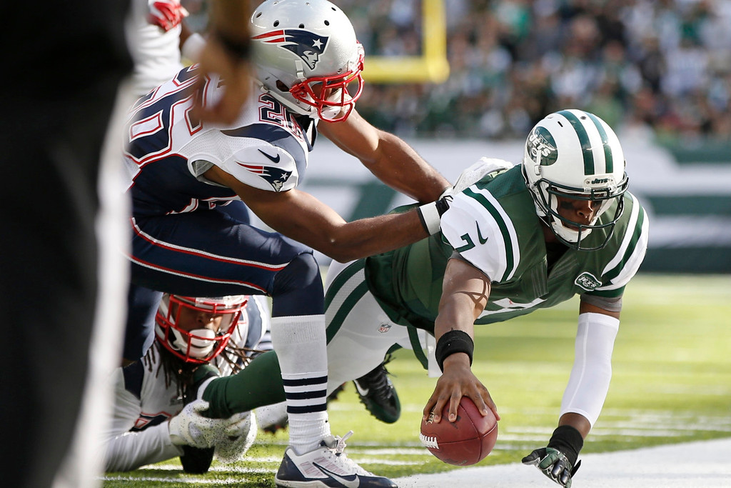 . New York Jets quarterback Geno Smith (7) dives out of bounds during the second half of an NFL football game against the New England Patriots on Sunday, Oct. 20, 2013, in East Rutherford, N.J.  (AP Photo/Kathy Willens)