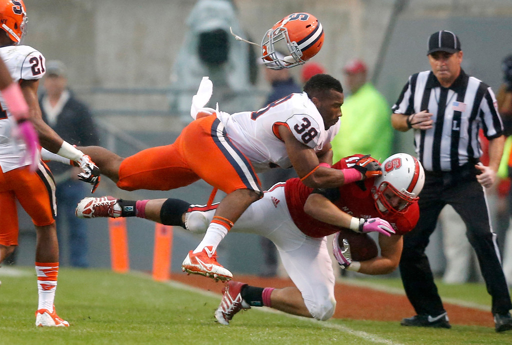 . Syracuse\'s Cameron Lynch (38) tackles North Carolina State\'s Tyler Purvis, right, during the second half of an NCAA college football game on Saturday, Oct. 12, 2013, at Carter-Finley Stadium in Raleigh, N.C. (AP Photo/The News & Observer,  Ethan Hyman)