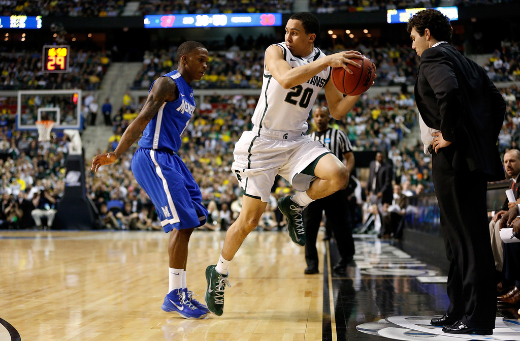 . AUBURN HILLS, MI - MARCH 23:  Travis Trice #20 of the Michigan State Spartans attempts to save the ball from going out of bounds against Joe Jackson #1 of the Memphis Tigers during the third round of the 2013 NCAA Men\'s Basketball Tournament at The Palace of Auburn Hills on March 23, 2013 in Auburn Hills, Michigan.  (Photo by Gregory Shamus/Getty Images)