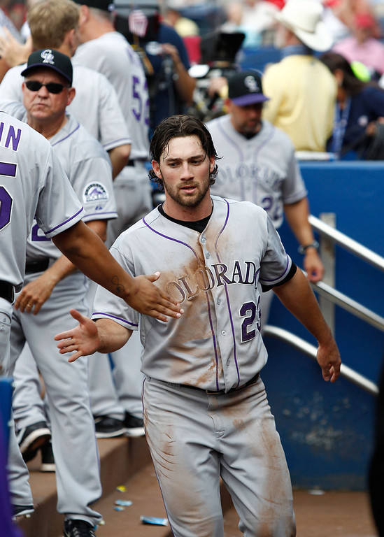 . Third baseman Charlie Culberson #23 of the Colorado Rockies is congratulated after scoring in the seventh inning of the game against the Atlanta Braves at Turner Field on May 24, 2014 in Atlanta, Georgia.  (Photo by Mike Zarrilli/Getty Images)