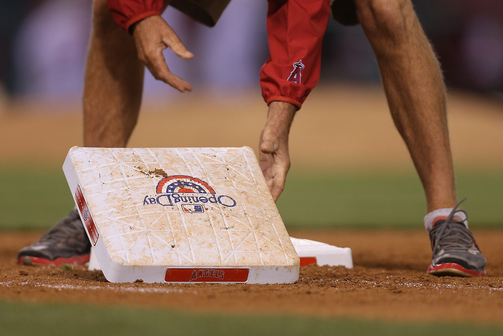 . Bases are changed out between innings during the Opening Day game between the Seattle Mariners and the Los Angeles Angels of Anaheim at Angel Stadium of Anaheim on March 31, 2014 in Anaheim, California.  (Photo by Jeff Gross/Getty Images)