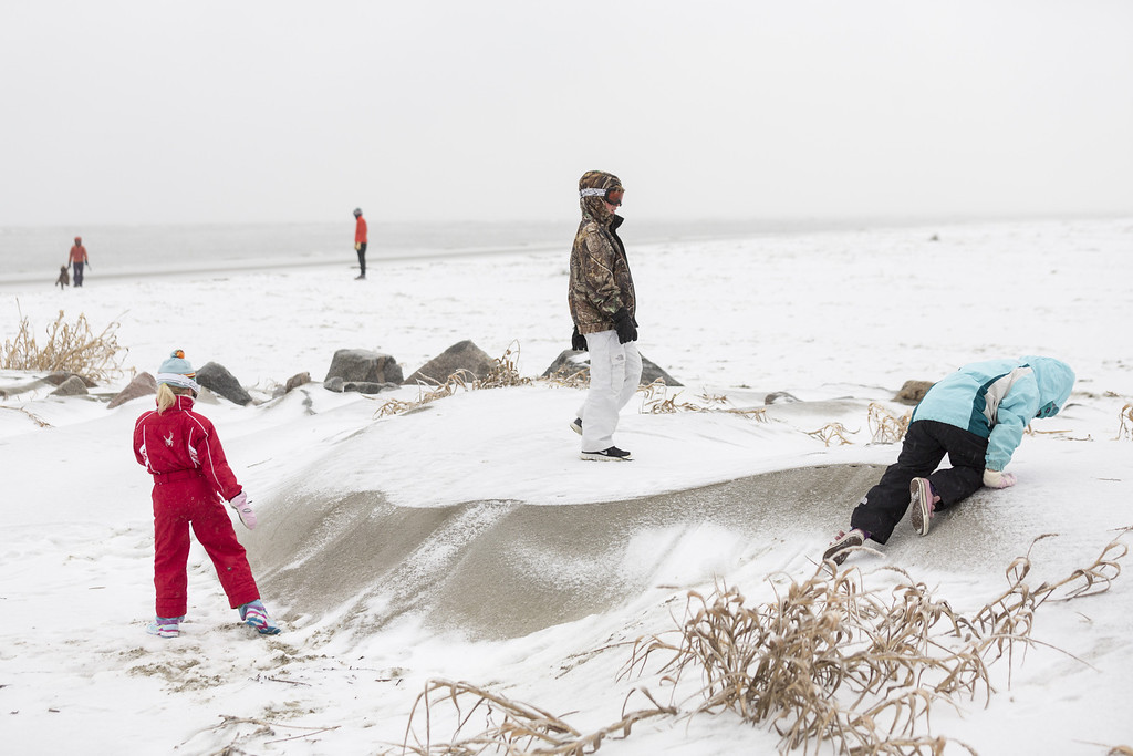 . Children play on a sand dune covered with snow after a rare ice storm blanked the normally warm historic city on January 29, 2014 in Charleston, South Carolina. The storm closed bridges and roads as a winter weather blanketed the region.   (Photo by Richard Ellis/Getty Images)