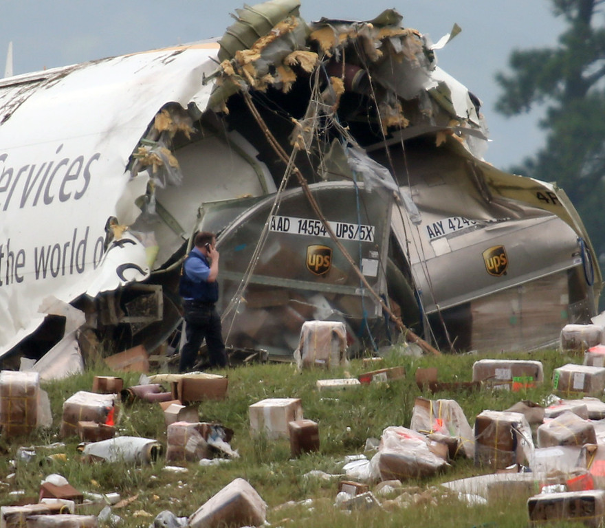 . A postal inspector officer looks over the debris of an UPS Airbus A300 cargo plane after it crashed on approach at Birmingham-Shuttlesworth International Airport  this morning Wednesday,  Aug. 14,  2013 in Birmingham, Ala.  (AP Photo/Hal Yeager)
