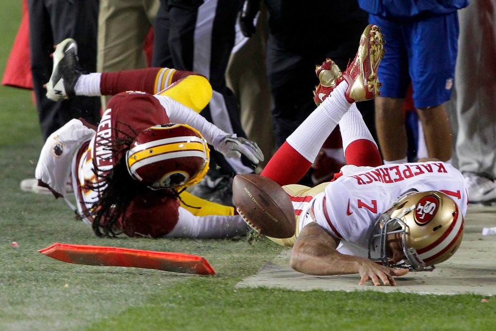 . Washington Redskins strong safety Brandon Meriweather collides with San Francisco 49ers quarterback Colin Kaepernick as they slide out-of-bounds during the second half of an NFL football game in Landover, Md., Monday, Nov. 25, 2013. The 49ers defeated the Redskins 27-6. (AP Photo/Mark Tenally)