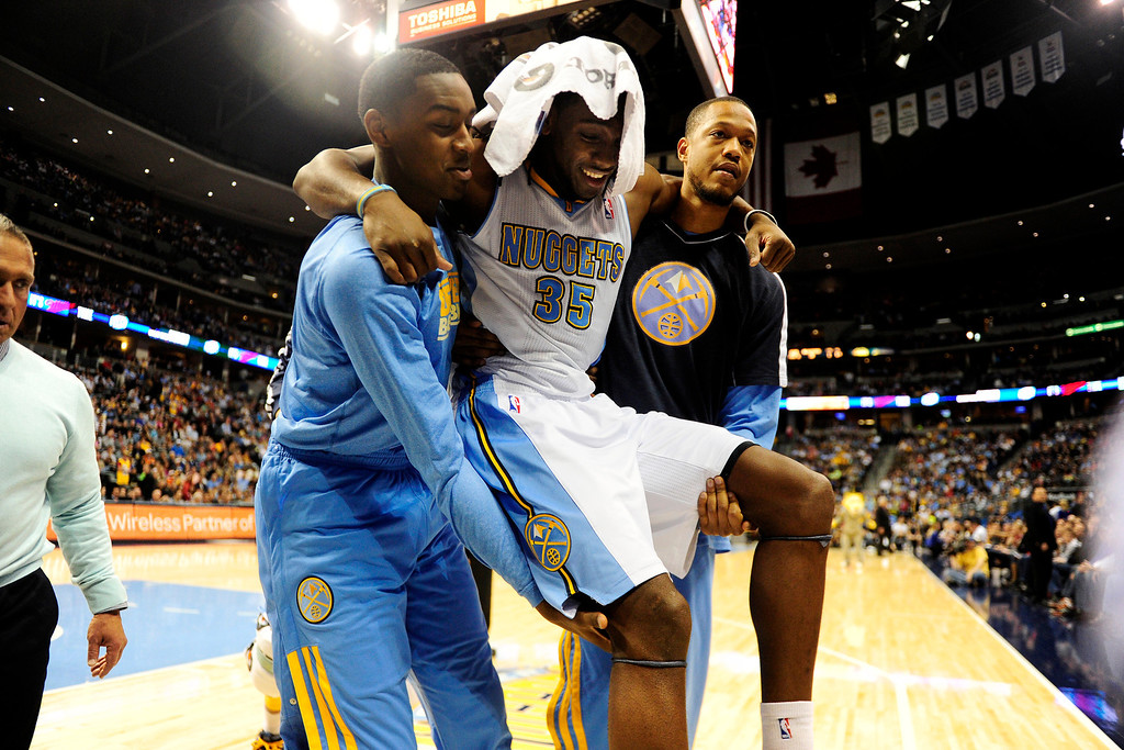 . DENVER, CO - APRIL 14: Kenneth Faried (35) of the Denver Nuggets gets carried off the court after suffering an injury during the first half of action. The Denver Nuggets play the Portland Trail Blazers at the Pepsi Center. (Photo by AAron Ontiveroz/The Denver Post)