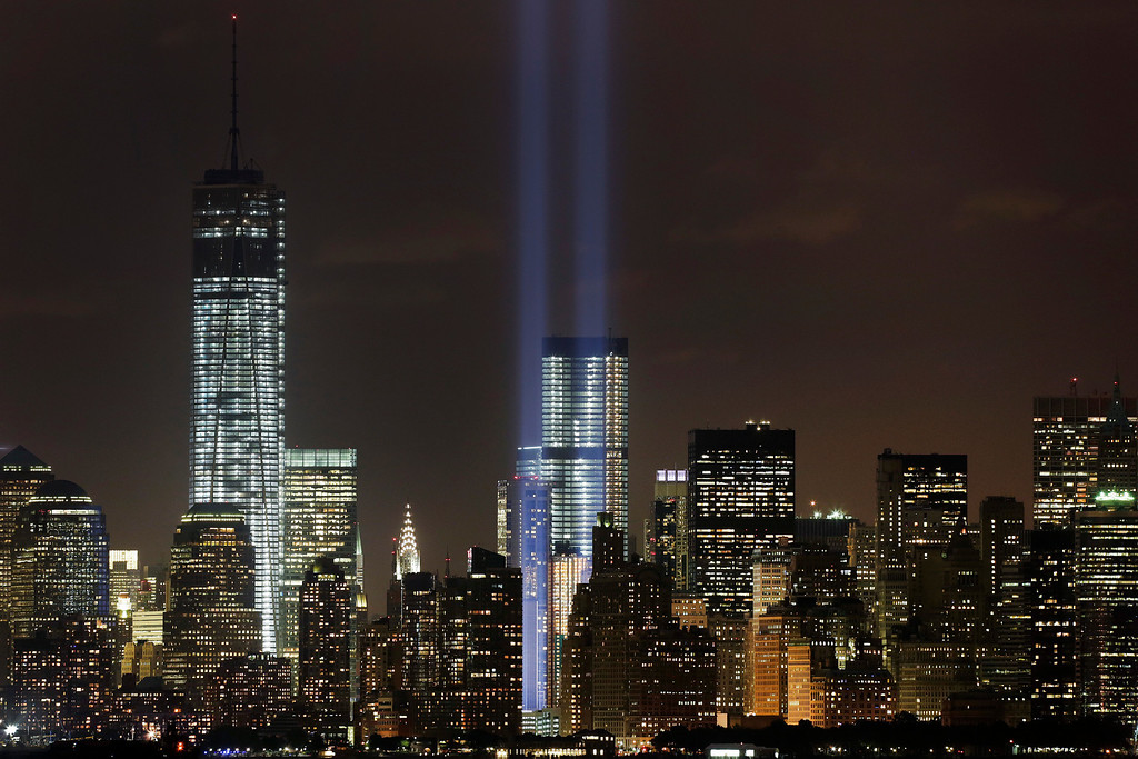 . CORRECTS YEAR OF TERROR ATTACKS TO 2001, INSTEAD OF 2011 - The Tribute in Light rises above the lower Manhattan skyline and Four World Trade Center, center, and One World Trade Center, left, in a test of the memorial light display, Monday, Sept. 9, 2013 in New York. The twin beams of light will also appear Wednesday, Sept. 11, twelve years after the terrorist attacks of Sept. 11, 2001. (AP Photo/Mark Lennihan)
