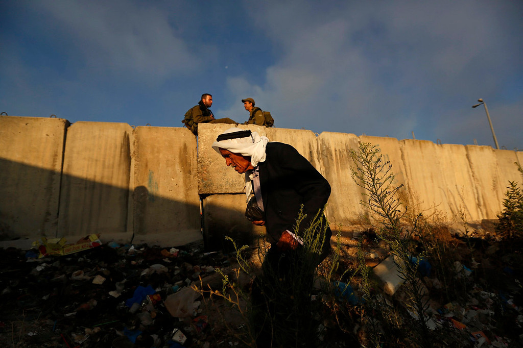 . Israeli soldiers sit near a part of Israel\'s controversial barrier as a Palestinian walks towards Qalandiya checkpoint near the West Bank city of Ramallah, during the holy month of Ramadan July 26, 2013. REUTERS/Mohamad Torokman