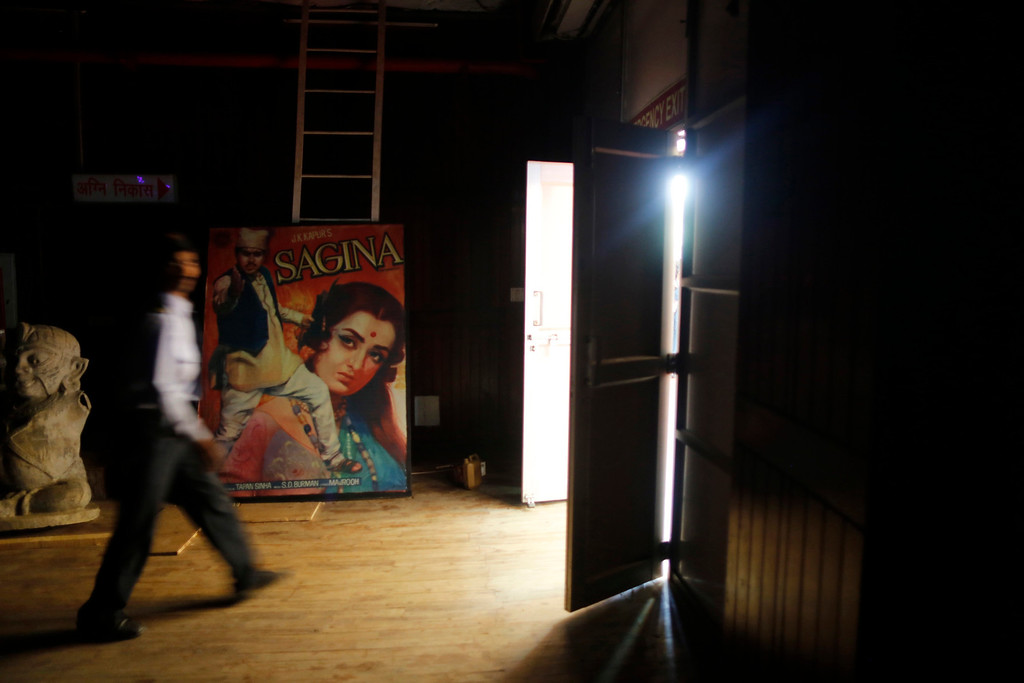 ". A security guard walks past a Hindi movie poster at an auditorium during a festival celebrating 100 years of Indian cinema in New Delhi April 30, 2013. Indian cinema marks 100 years since Dhundiraj Govind Phalke\'s black-and-white silent film ""Raja Harishchandra\"" (King Harishchandra) held audiences spellbound at its first public screening on May 3, 1913, in Mumbai. Indian cinema, with its subset of Bollywood for Hindi-language films, is now a billion-dollar industry that makes more than a thousand films a year in several languages. It is worth 112.4 billion rupees (over $2 billion) and leads the world in terms of films produced and tickets sold. Picture taken April 30, 2013. REUTERS/Anindito Mukherjee"