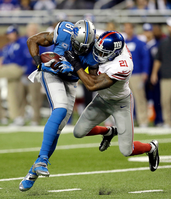 . Detroit Lions wide receiver Calvin Johnson (81) is stopped by New York Giants free safety Ryan Mundy (21) during the first quarter of an NFL football game, Sunday, Dec. 22, 2013, in Detroit. (AP Photo/Carlos Osorio)