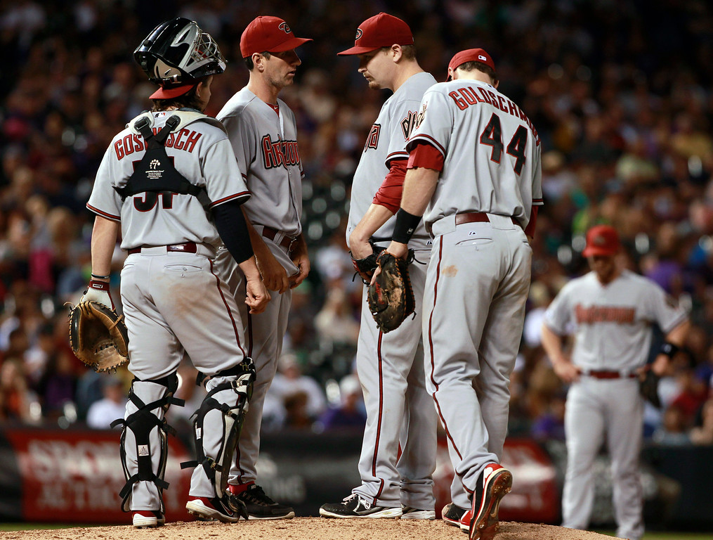 . Arizona Diamondbacks starting pitcher Trevor Cahill, third from left, confers with catcher Tuffy Gosewisch, left, pitching coach Charles Nagy, second from left, and first baseman Paul Goldschmidt after Cahill gave up two singles to the Colorado Rockies in the sixth inning of a baseball game in Denver on Saturday, Sept. 21, 2013. (AP Photo/David Zalubowski)