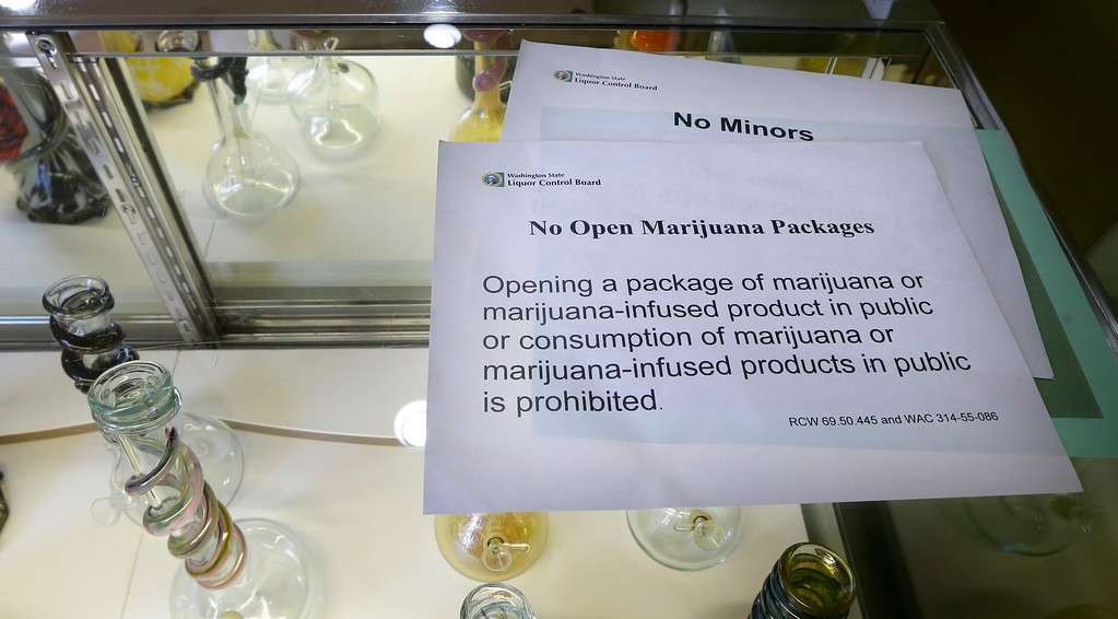 . A sign noting the Washington state law that prohibits opening packages that contain marijuana or marijuana-infused products in public rests on a glass case displaying bongs for sale Monday, July 7, 2014, at the recreational marijuana store Cannabis City in Seattle. The store will be the first and only store in Seattle to initially sell recreational marijuana when legal sales begin on Tuesday, July 8, 2014. (AP Photo/Ted S. Warren)