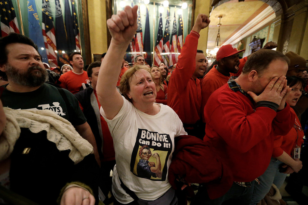 . Protesters gather for a rally in the rotunda at the State Capitol in Lansing, Mich., Tuesday, Dec. 11, 2012. The crowd is protesting right-to-work legislation passed last week. Michigan could become the 24th state with a right-to-work law next week. Rules required a five-day wait before the House and Senate vote on each other\'s bills; lawmakers are scheduled to reconvene Tuesday and Gov. Snyder has pledged to sign the bills into law. (AP Photo/Paul Sancya)