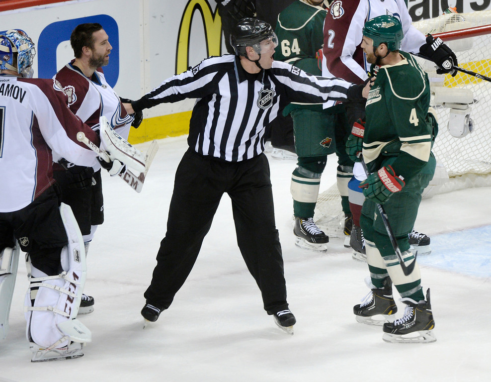 . An official separated Colorado center Maxime Benoit (25) and Minnesota defenseman Clayton Stoner (4) in the first period. The Minnesota Wild hosted the Colorado Avalanche at the Xcel Energy Center in St. Paul Monday night, April 21, 2014. (Photo by Karl Gehring/The Denver Post)