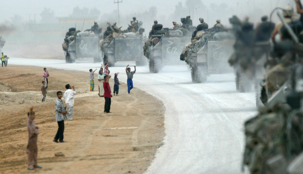 . Iraqis wave to armored attack vehicles from the U.S. Marines of Task Force Tarawa April 7, 2003 as they move through central Iraq. The Marines were sweeping through the country looking for enemy forces as the war in Iraq continued. (Photo by Joe Raedle/Getty Images)
