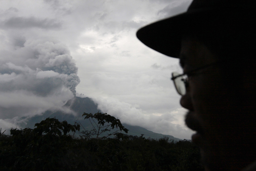 . A villager watches as Mount Sinabung erupts in Simpang Empat, North Sumatra, Indonesia, Sunday, Nov. 3, 2013. Officials raised the volcano\'s alert status to the second-highest level after the 2,600-meter (8,530-foot) -high mountain erupted early Sunday. (AP Photo/Ade Sinuhaji)