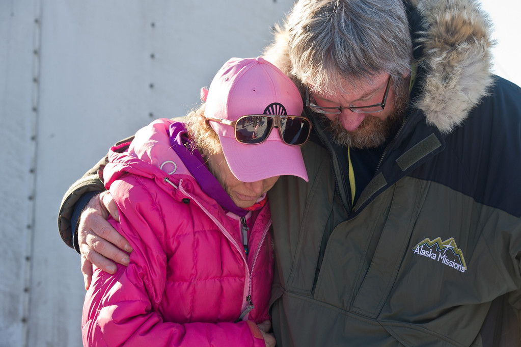 . Musher DeeDee Jonrowe prays with Scott Jenkins of Alaska Missions before the start of the Iditarod Trail Sled Dog Race on Willow Lake, Sunday, March 2, 2014, in Willow, Alaska. The race will take mushers nearly a thousand miles to the finish line in Nome, on Alaska\'s western coast. (AP Photo/Anchorage Daily News, Marc Lester)