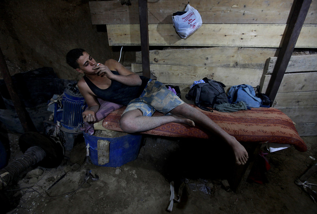 . In this Monday, Sept. 30, 2013 photo, a Palestinian worker smokes a cigarette inside a smuggling tunnel along the border with Egypt in Rafah, southern Gaza Strip. Gaza�s tunnel smugglers along the border with Egypt are mostly idle these days. Some rest on cots in the dank underground pathways, stretching out for a smoke. Others pass the time cleaning the small carts on wheels that are normally pulled through the tunnels carrying cement or consumer goods from Egypt. Since the summer, Egypt�s military has tried to destroy or seal off most of the smuggling tunnels under the Gaza-Egypt border, a consequence of the heightened tensions between Cairo and the Hamas government in Gaza. (AP Photo/Hatem Moussa)