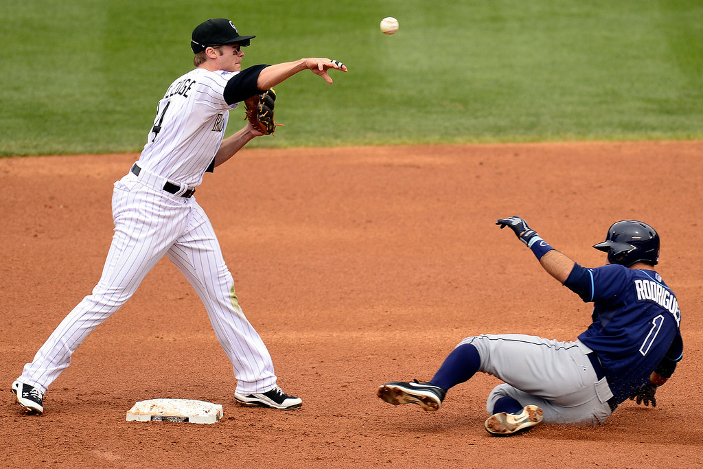 . DENVER, CO - MAY 5: Josh Rutledge (14) of the Colorado Rockies turns a double play as Sean Rodriguez (1) of the Tampa Bay Rays slides into second during the Rockies\' 8-3 loss.   (Photo by AAron Ontiveroz/The Denver Post)