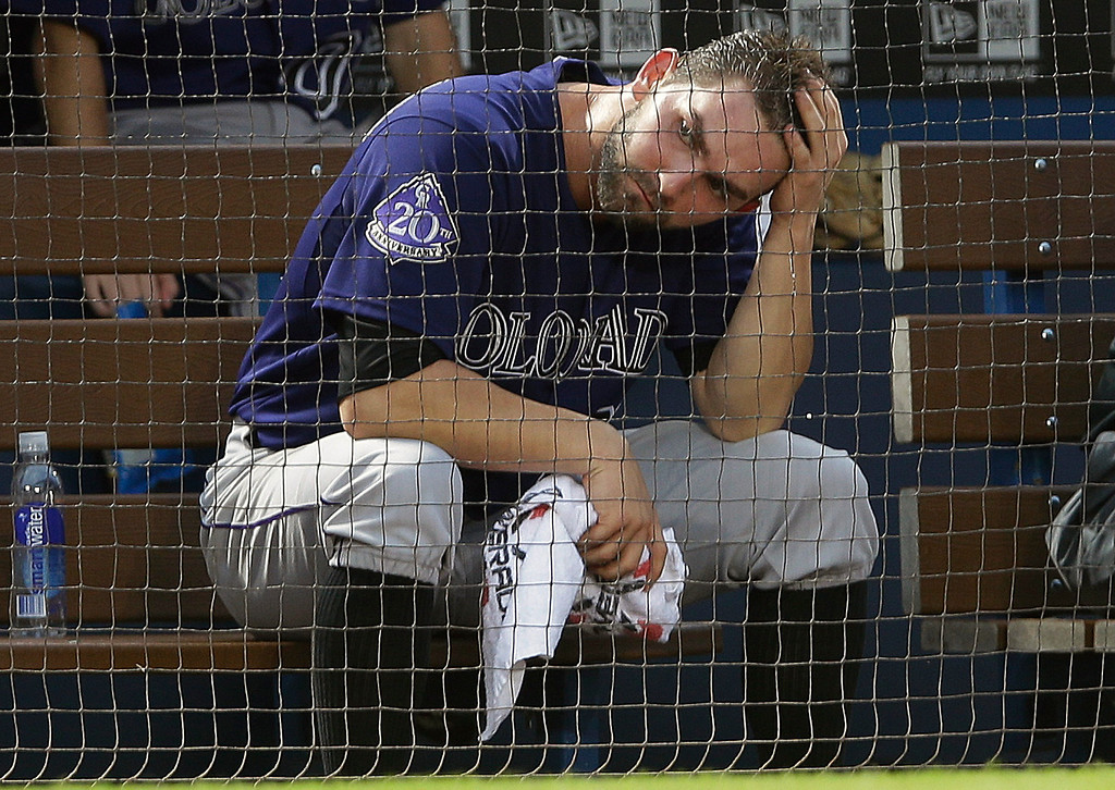 . Colorado Rockies starting pitcher Tyler Chatwood sits in the dugout after being pulled in the third inning of a baseball game against the Atlanta Braves in Atlanta, Wednesday, July 31, 2013. (AP Photo/John Bazemore)
