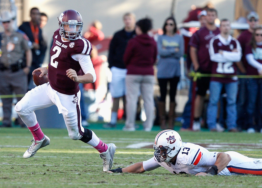 . Texas A&M quarterback Johnny Manziel (2) avoids the grasp of Auburn defensive end Craig Sanders (13) in the third quarter during an NCAA college football game Saturday, Oct. 19, 2013, in College Station, Texas. Auburn won 45-41. (AP Photo/Bob Levey)