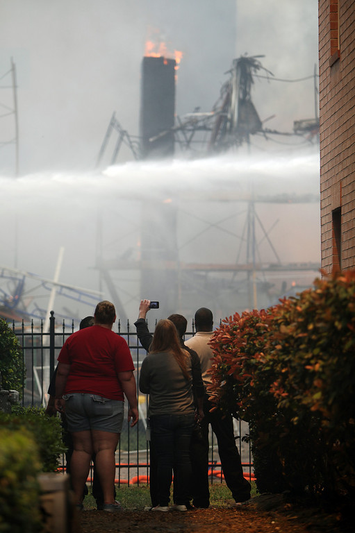 . People take photos as Houston firefighters work to extinguish a five-alarm fire at a construction site Tuesday, March 25, 2014, in Houston. (AP Photo/Houston Chronicle, Mayra Beltran)