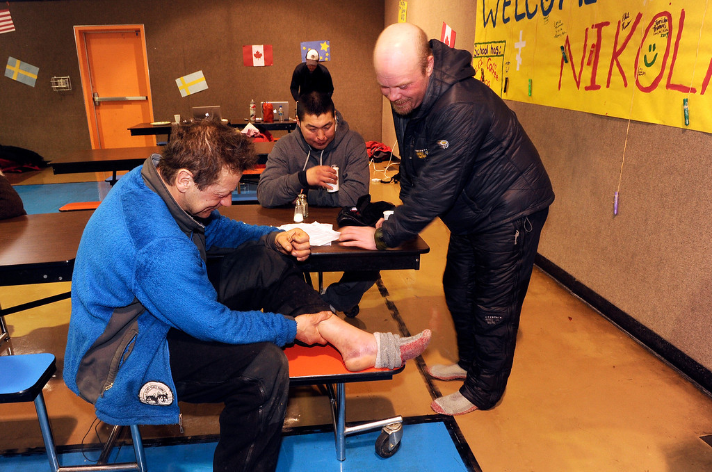 . Martin Buser, left, shows his swollen ankle to Aaron Burmeister in the school cafeteria during the 2014 Iditarod Trail Sled Dog Race on Tuesday, March 4, 2014, in Nikolai, Alaska. The swelling of Buser\'s ankle has gone down after a short rest at the Nikolai checkpoint. Burmeister injured his knee about 18 miles past the Rohn checkpoint on the snowless Farewell Burn. His knee popped out and he had to tape it up so it would stay in place. (AP Photo/The Anchorage Daily News, Bob Hallinen)