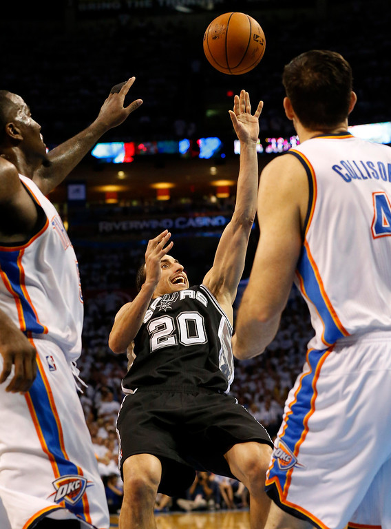 . As he falls to the floor, San Antonio Spurs guard Manu Ginobili (20) shoots between Oklahoma City Thunder\'s Kendrick Perkins, left, and Nick Collison (4) in the second half of Game 6 of the Western Conference finals NBA basketball playoff series in Oklahoma City, Saturday, May 31, 2014. (AP Photo/Sue Ogrocki)