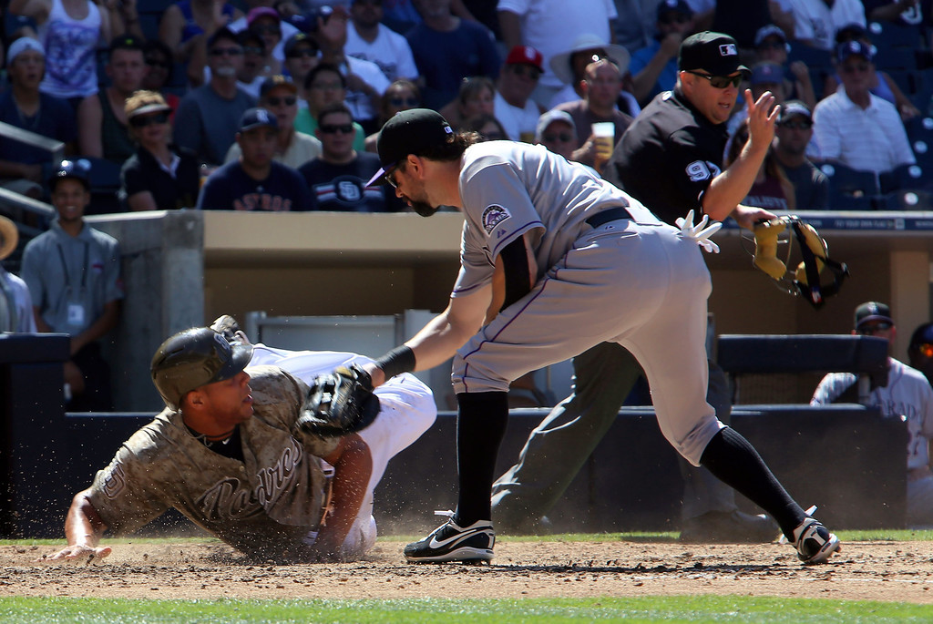 . Colorado Rockies first baseman Todd Helton, front right, puts a tag on San Diego Padres\' Kyle Blanks, left, at home as home plate umpire Todd Tichenor, back right, calls Blanks out for running outside of the base line in the fifth inning during the baseball game on Sunday, Sept. 8, 2013, in San Diego. (AP Photo/Don Boomer)