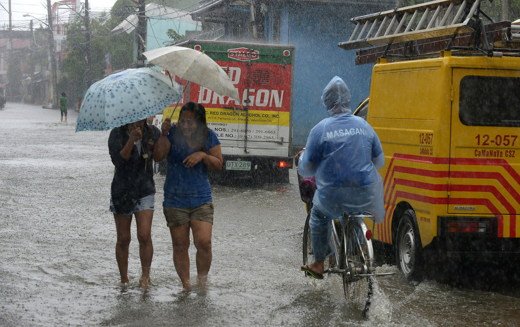 . Residents wade through ankle-deep water along a flooded stretch of road as heavy rains brought on by Typhoon Utor hit the suburbs of Manila on August 12, 2013.  The strongest typhoon to hit the Philippines this year flattened houses and triggered landslides in remote towns on August 12, killing at least one person and leaving 23 others missing, authorities said.   JAY DIRECTO/AFP/Getty Images
