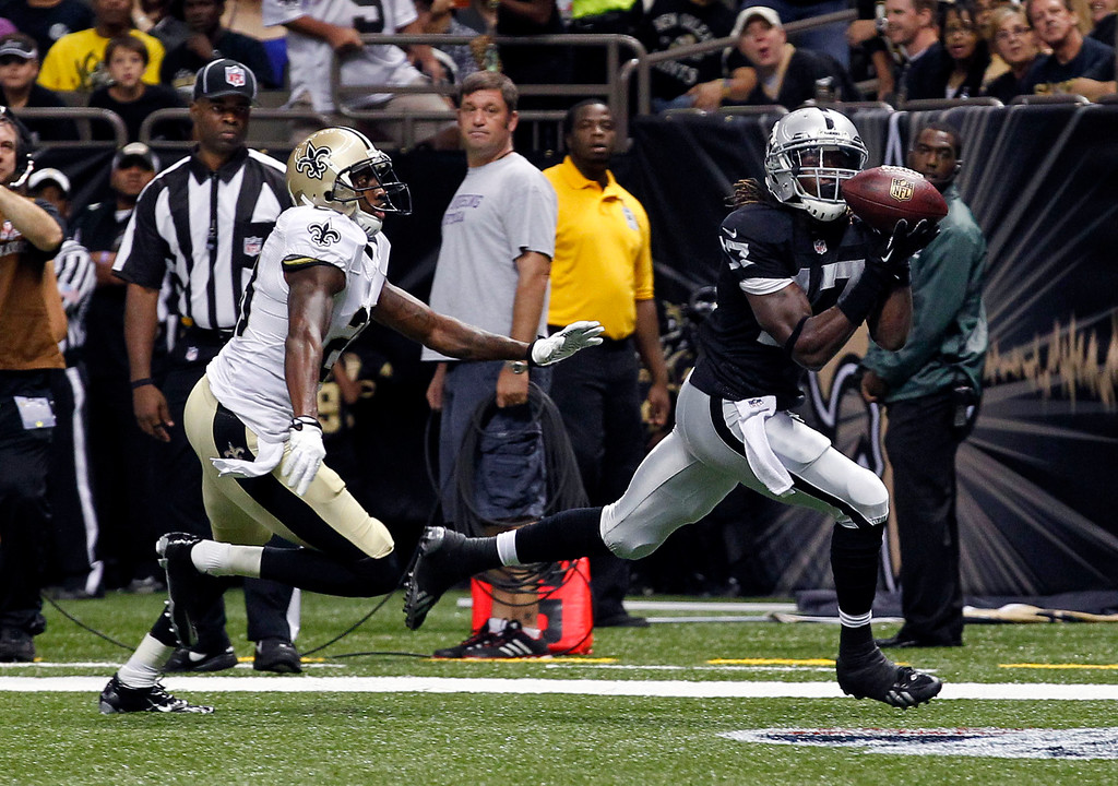 . Oakland Raiders wide receiver Denarius Moore (17) pulls in a touchdown pass in front of New Orleans Saints cornerback Keenan Lewis (28) in the first half of an NFL preseason football game at the Mercedes-Benz Superdome in New Orleans, Friday, Aug. 16, 2013. (AP Photo/Jonathan Bachman)