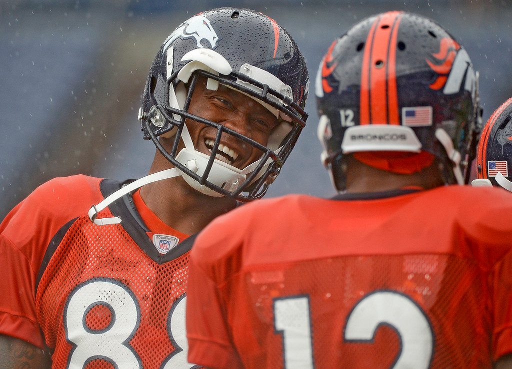 . Denver Broncos wide receiver Demaryius Thomas (88) shares a laugh with Denver Broncos wide receiver Andre Caldwell (12)  during a rain day on day six of the Denver Broncos 2014 training camp July 30, 2014 at Sports Authority Field at Mile High Stadium.  (Photo by John Leyba/The Denver Post)