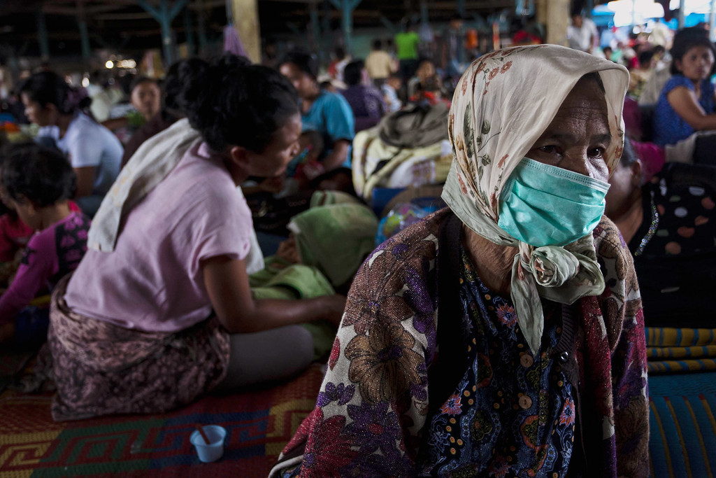 . A woman wears a mask at a temporary evacuation shelter at Tiga Binanga village on November 26, 2013 in Karo District, North Sumatra, Indonesia.  (Photo by Ulet Ifansasti/Getty Images)