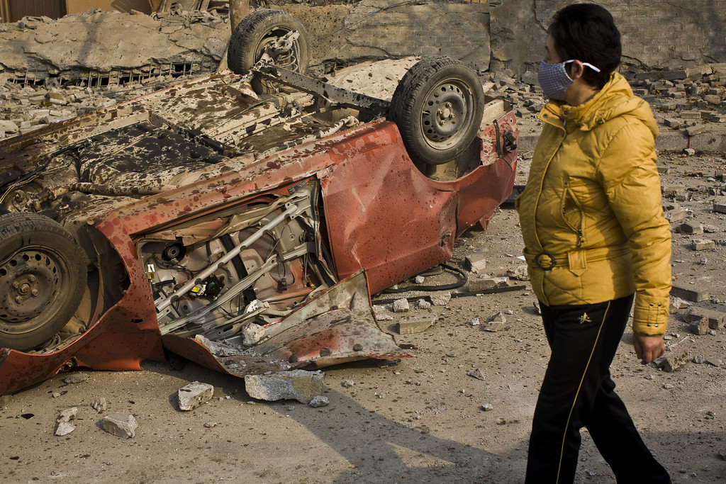 . A damaged vehicle lies by a street after an oil pipeline exploded, ripping roads apart, turning cars over and sending thick black smoke billowing over the city of Qingdao, east China\'s Shandong province on November 22, 2013, killing 35 people, authorities said, in the latest deadly industrial accident in the country.    AFP PHOTOSTR/AFP/Getty Images