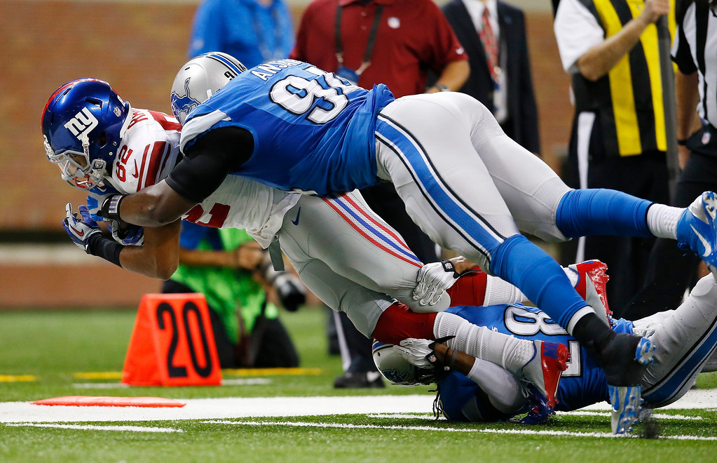 . Detroit Lions defensive end Ezekiel Ansah (94) tackles New York Giants wide receiver Rueben Randle (82) during the second quarter of an NFL football game, Sunday, Dec. 22, 2013, in Detroit. (AP Photo/Rick Osentoski)