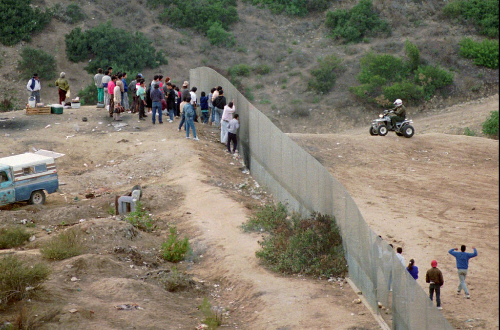 . An unidentified U.S Border Patrol agent, right top, watches a group of people waiting to cross the U.S./Mexico border illegally Tuesday, March 5, 1996, in eastern San Diego county. The San Diego Sheriff\'s Department announced Wednesday Dec. 18, 1996, that they would be assigning six officers to assist the U.S. Border Patrol in stemming the flow of drugs in eastern San Diego county. (AP Photo/Denis Poroy)