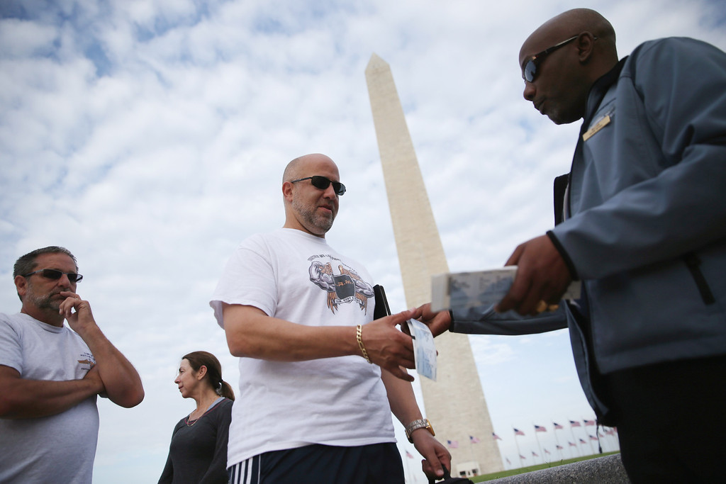 . William Davenport (R), an employee of Eastern National which runs the bookstore of the Washington Monument, hands out tickets to visitors May 12, 2014 on the ground of the monument in Washington, DC.  (Photo by Alex Wong/Getty Images)