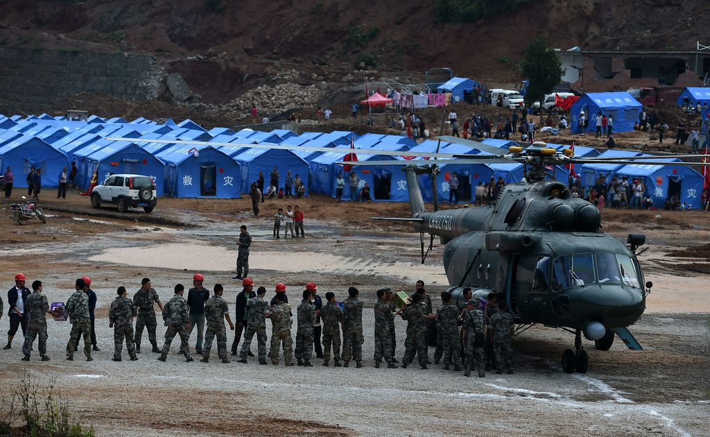 . Supplies are offloaded from a military helicopter at Longtoushan, in China\'s southwest Yunnan province on August 5, 2014. AFP PHOTO/Greg BAKER/AFP/Getty Images