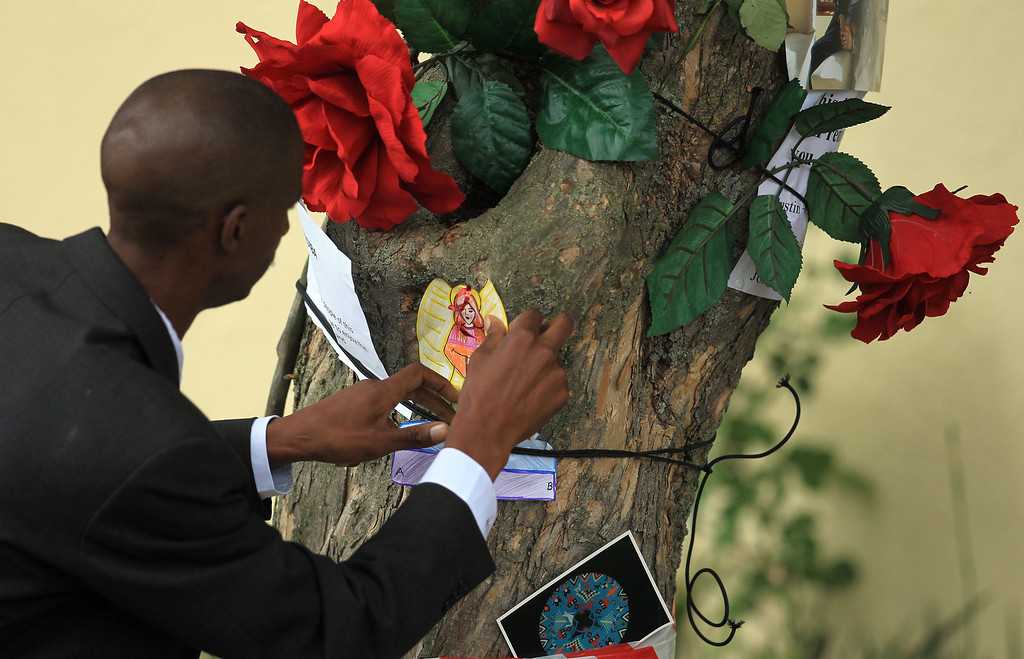 . A security person attaches a hand made card from mourners outside the home of former president Nelson Mandela in Johannesburg, South Africa, Friday, Dec. 6, 2013, after he died Thursday night following a long illness. (AP Photo/Themba Hadebe)