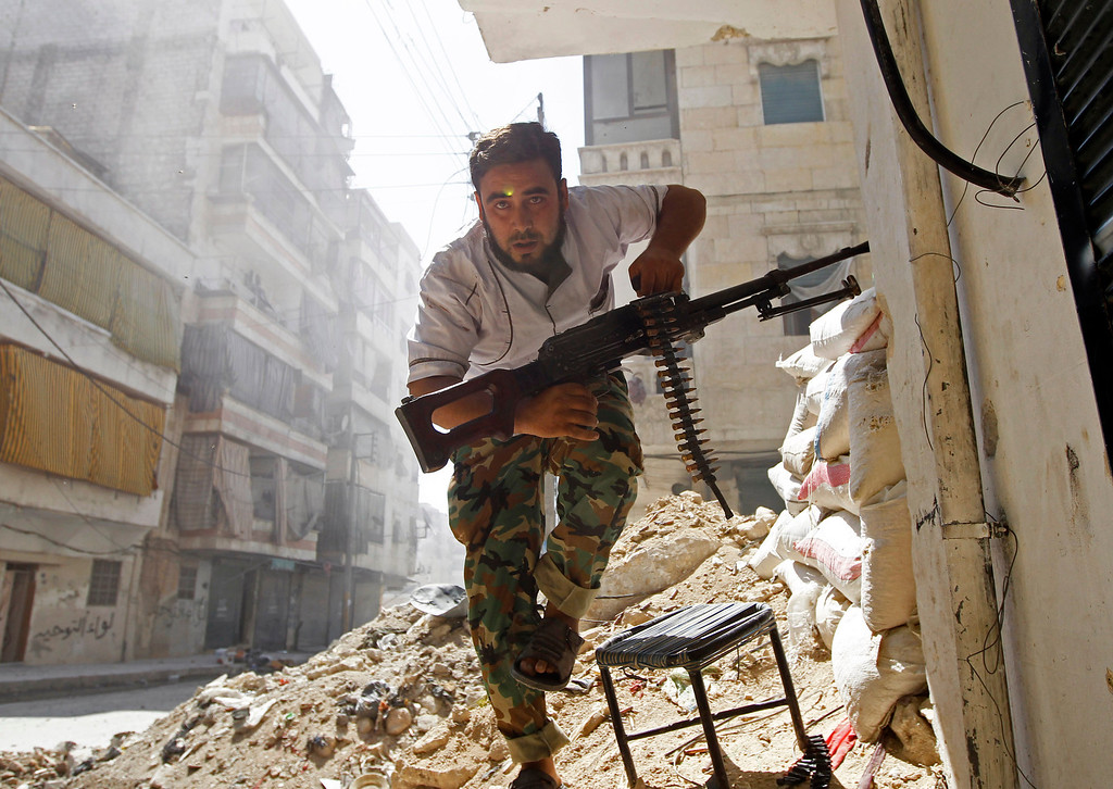 . A Free Syrian Army fighter takes cover during clashes with Syrian Army in the Salaheddine neighbourhood of central Aleppo August 7, 2012.  REUTERS/Goran Tomasevic
