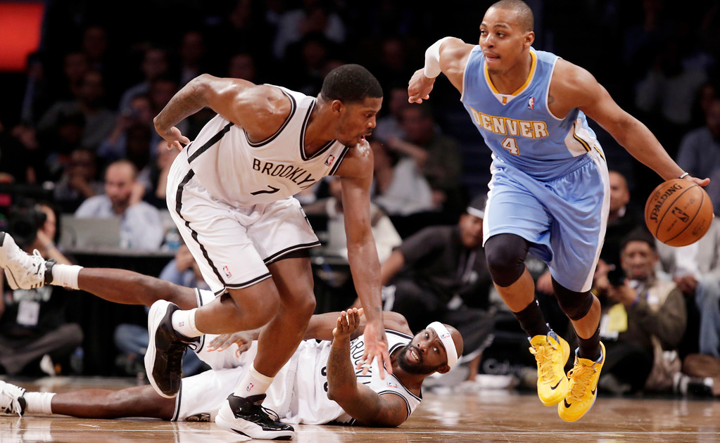. Denver Nuggets guard Randy Foye (4) runs down court leaving Brooklyn Nets forward Reggie Evans, bottom center, and Brooklyn Nets guard Joe Johnson (7) in his wake in the second half of an NBA basketball game Tuesday, Dec. 3, 2013, in New York. The Nuggets won 111-87. (AP Photo/Kathy Willens)