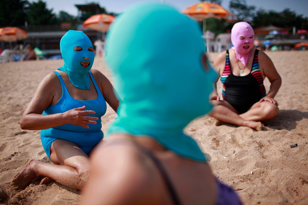 . Women, wearing nylon masks, rest on the shore during their visit to a beach in Qingdao, Shandong province July 6, 2012. The mask, which was invented by a woman about seven years ago, is used to block the sun\'s rays. The mask is under mass production and is on sale at local swimwear stores. REUTERS/Aly Song