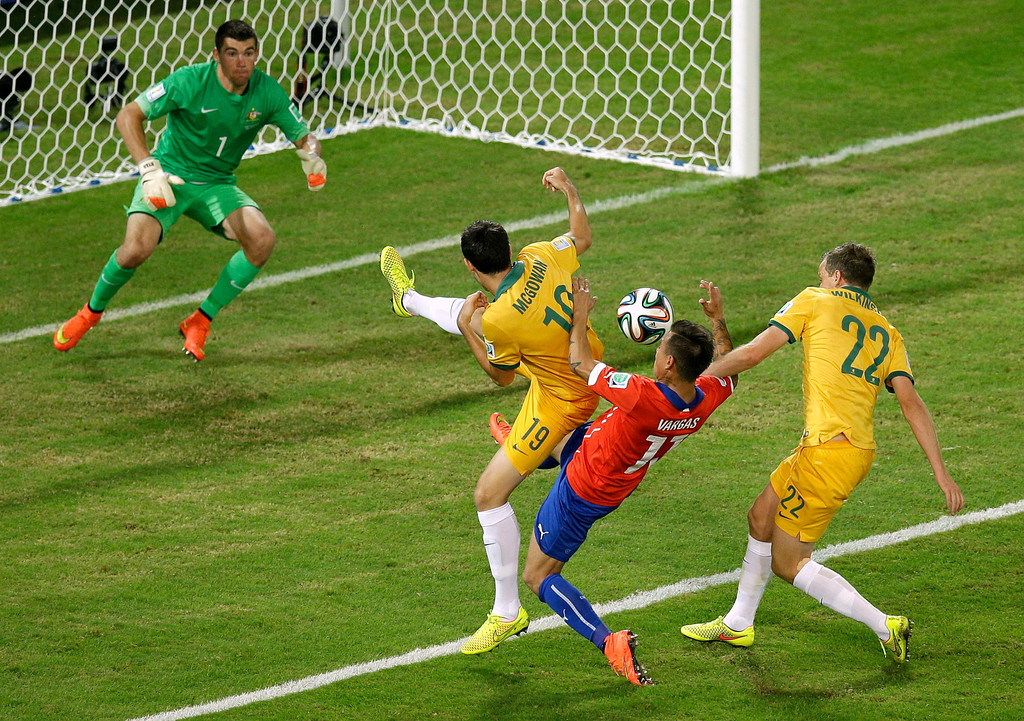 . Chile\'s Eduardo Vargas, second right, fights for the ball with Australia\'s Ryan McGowan, left, and Australia\'s Alex Wilkinson during the group B World Cup soccer match between Chile and Australia in the Arena Pantanal in Cuiaba, Brazil, Friday, June 13, 2014. (AP Photo/Michael Sohn)