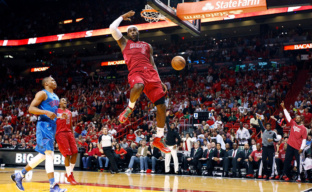 . Miami Heat\'s LeBron James (6) dunks as Oklahoma City Thunder\'s Russell Westbrook (0) and Heat\'s Mario Chalmers (15) watch during the first half of an NBA basketball game, Tuesday, Dec. 25, 2012, in Miami. (AP Photo/J Pat Carter)
