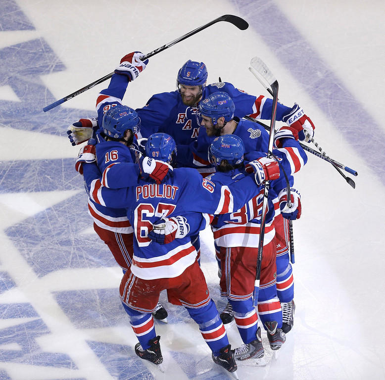 . New York Rangers left wing Benoit Pouliot (67) celebrates with teammates after scoring in the first period during Game 4 of the NHL hockey Stanley Cup Final against the Los Angeles Kings, Wednesday, June 11, 2014, in New York. (AP Photo/Seth Wenig)