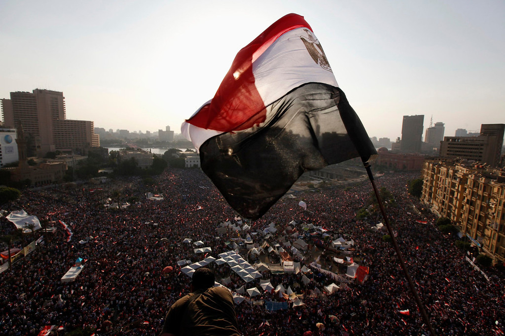 . An Egyptian flag is seen as protesters opposing Egyptian President Mohamed Mursi shout slogans against him and Brotherhood members during a protest at Tahrir Square in Cairo June 30, 2013. Egyptians poured onto the streets on Sunday, swelling crowds that opposition leaders hope will number into the millions by evening and persuade Islamist President Mohamed Mursi to resign.  REUTERS/Mohamed Abd El Ghany